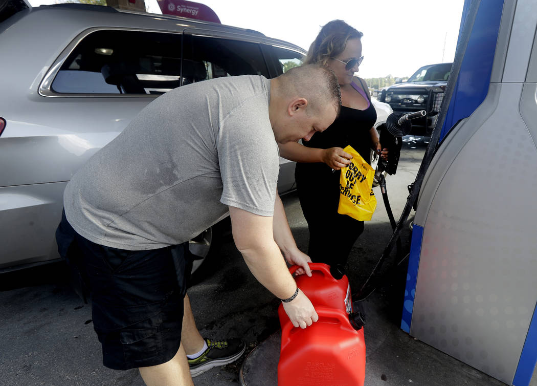 "Sarah Dankanich, right, removes an ""out of service"" wrapper from a gas pump as her husband, Bryan Dankanich, left, prepares to pump gas in cans in advance of Hurricane Florence in Wilmin ..."
