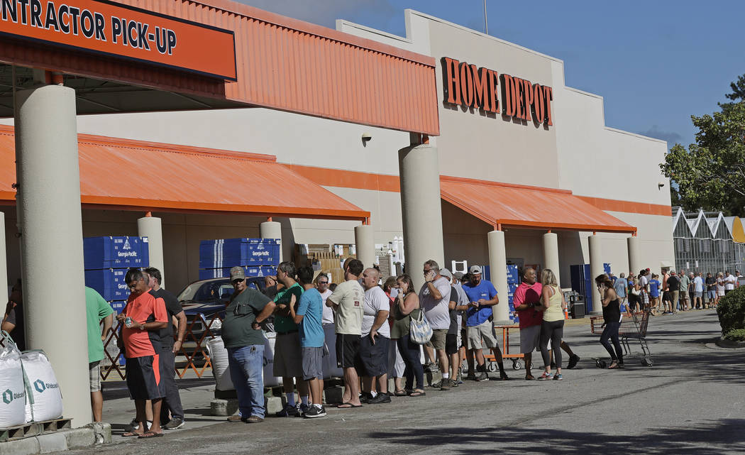 People line up outside a Home Depot for a new supply of generators and plywood in advance of Hurricane Florence in Wilmington, N.C., Wednesday, Sept. 12, 2018. Florence exploded into a potentially ...