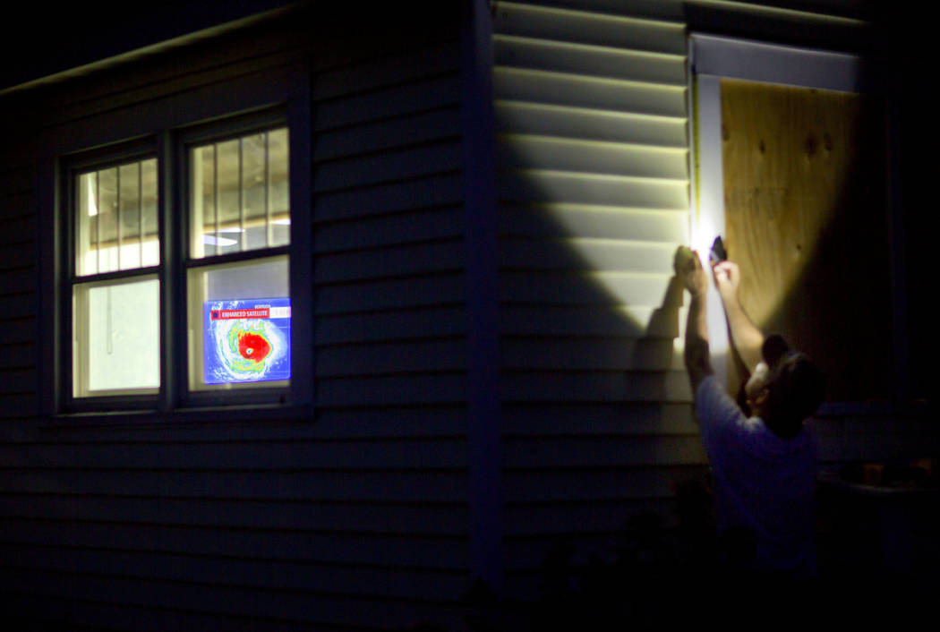 Rob Muller boards up his home as a satellite image of Hurricane Florence is broadcast on a television inside in Morehead City, N.C., Tuesday, Sept. 11, 2018. Florence exploded into a potentially c ...