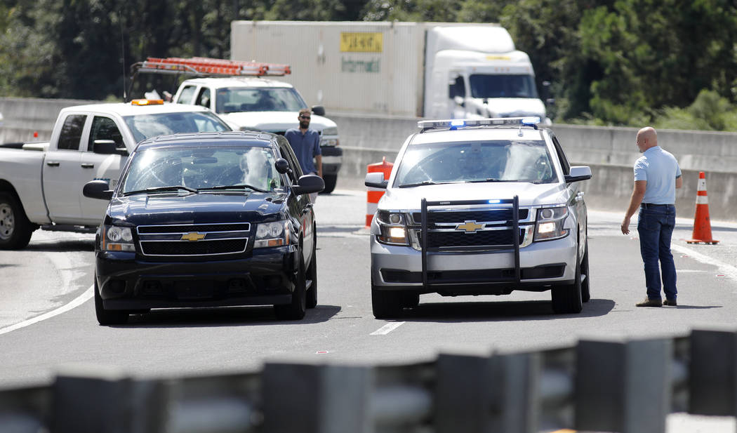 Police cars block the Ashley Phosphate Road exit ramp off Interstate 26 in North Charleston, S.C., as both sides of the highway flow westbound toward Columbia, S.C., Tuesday, Sept. 11, 2018, in pr ...