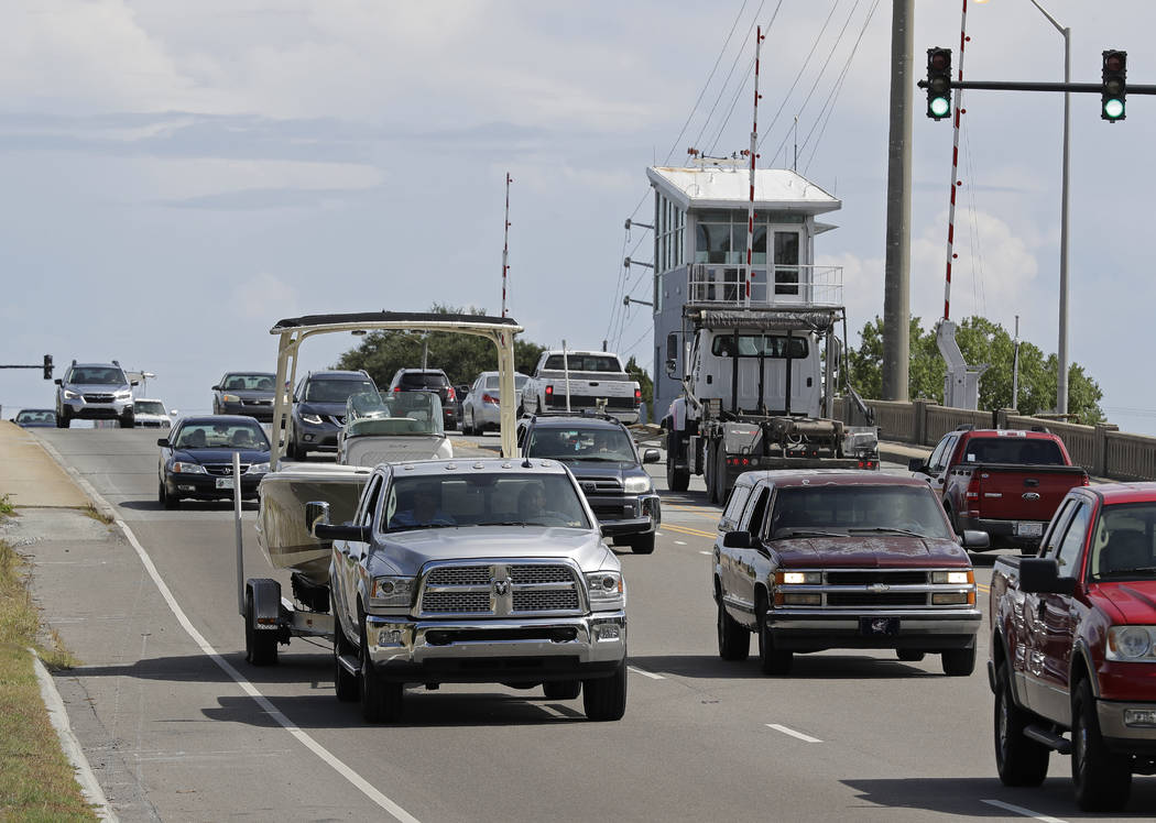 People drive over a drawbridge in Wrightsville Beach, N.C., as they evacuate the area in advance of Hurricane Florence, Tuesday, Sept. 11, 2018. Florence exploded into a potentially catastrophic h ...