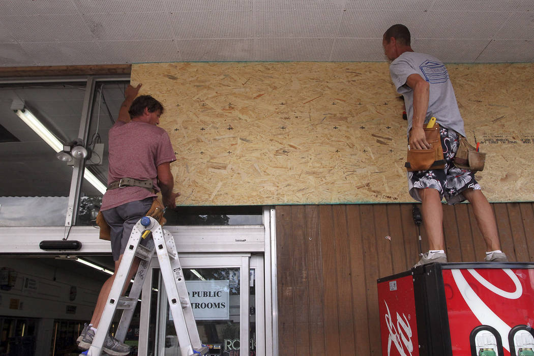 Robert Patch and John Courtney, of Local Builder's Construction, install wood paneling over windows at the Armstrong Grocery , Tuesday, Sept. 11, 2018, in New Bern, N.C., as storeowners and reside ...