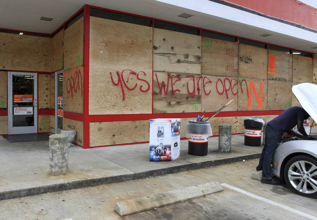 An auto parts store has wood paneling installed over the windows, Tuesday, Sept. 11, 2018, in New Bern, N.C., as a precaution against storm damage from Hurricane Florence. (Gray Whitley/Sun Journ ...