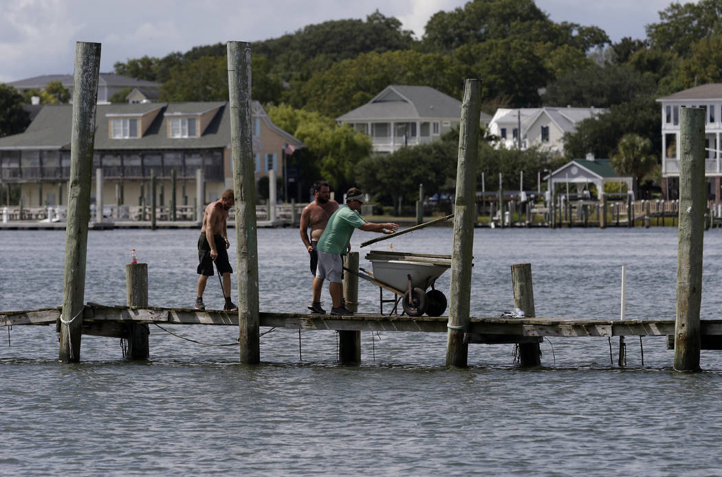 From left, Josh Clappsy, Blake Price, and JB Phillips remove boards from a dock in hopes to save it from rising waters in Swansboro, N.C., Tuesday, Sept. 11, 2018. Florence exploded into a potenti ...