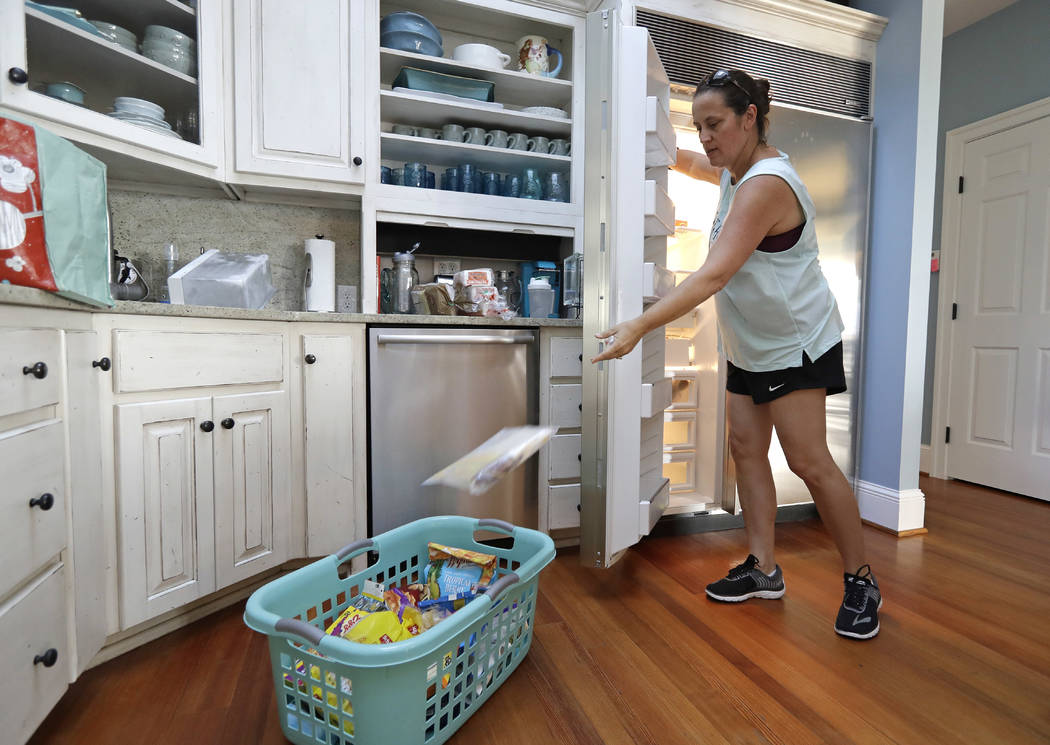 Michelle Stober, of Cary, N.C., removes food from a freezer as she prepares their vacation home in advance of Hurricane Florence in Wrightsville Beach, N.C., Tuesday, Sept. 11, 2018. Florence expl ...