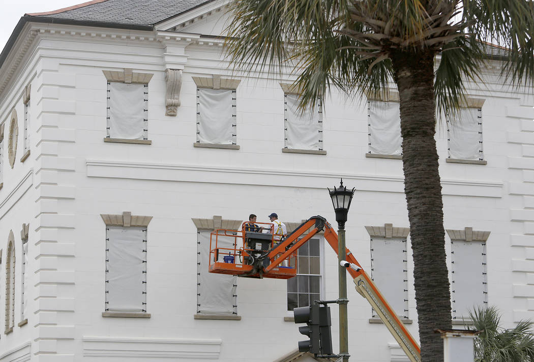 Workers cover the windows of the historic Charleston County Courthouse in Charleston, S.C., in preparation for the advancing Hurricane Florence Tuesday, Sept. 11, 2018. (AP Photo/Mic Smith)