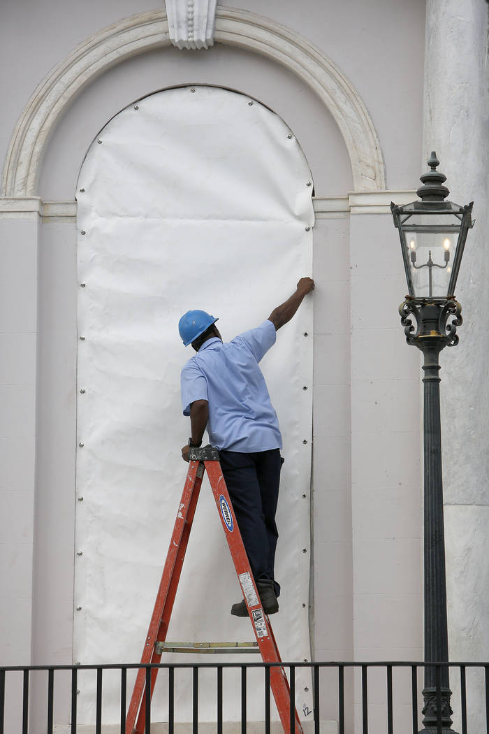A worker covers a window at Charleston City Hall in Charleston, S.C., in preparation for the advancing Hurricane Florence Tuesday, Sept. 11, 2018. (AP Photo/Mic Smith)