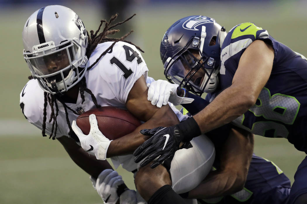 Oakland Raiders wide receiver Keon Hatcher (14) is tackled by Seattle Seahawks linebacker Austin Calitro, right, during the first half of an NFL football preseason game, Thursday, Aug. 30, 2018, i ...