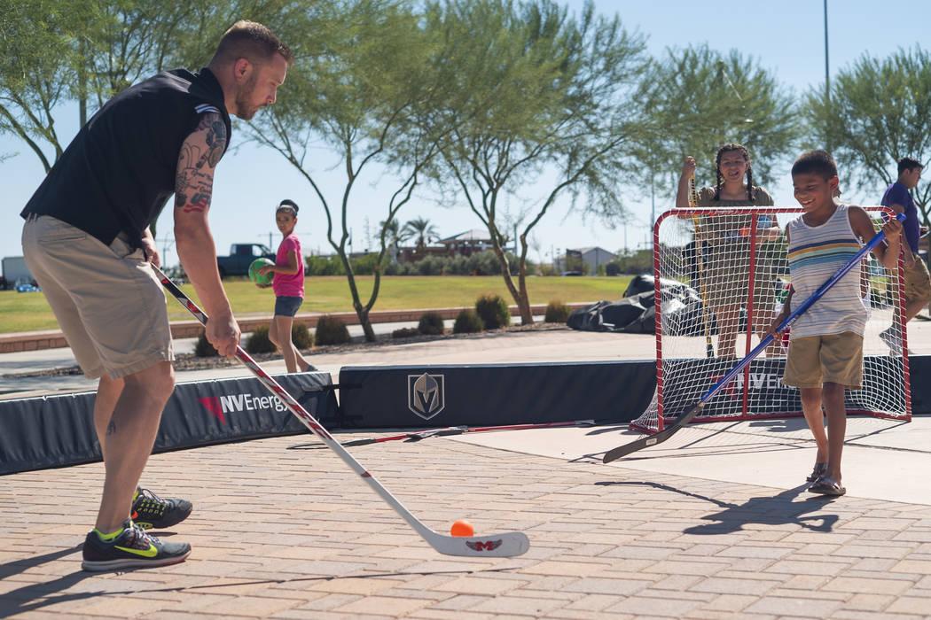 Alex Gomez, 9, learns how to play hockey from Vegas Golden Knights youth hockey senior manager Matt Flynn at the El Tiempo Fiesta Las Vegas at Craig Ranch Regional Park in North Las Vegas, Saturda ...