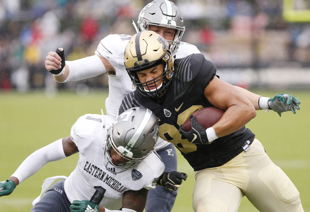 Purdue tight end Brycen Hopkins is brought down by Eastern Michigan's Jalen Phelps (1) and Kyle Rachwal after a pass reception in the first half of an NCAA football game Saturday, Sept. 8, 2018, i ...
