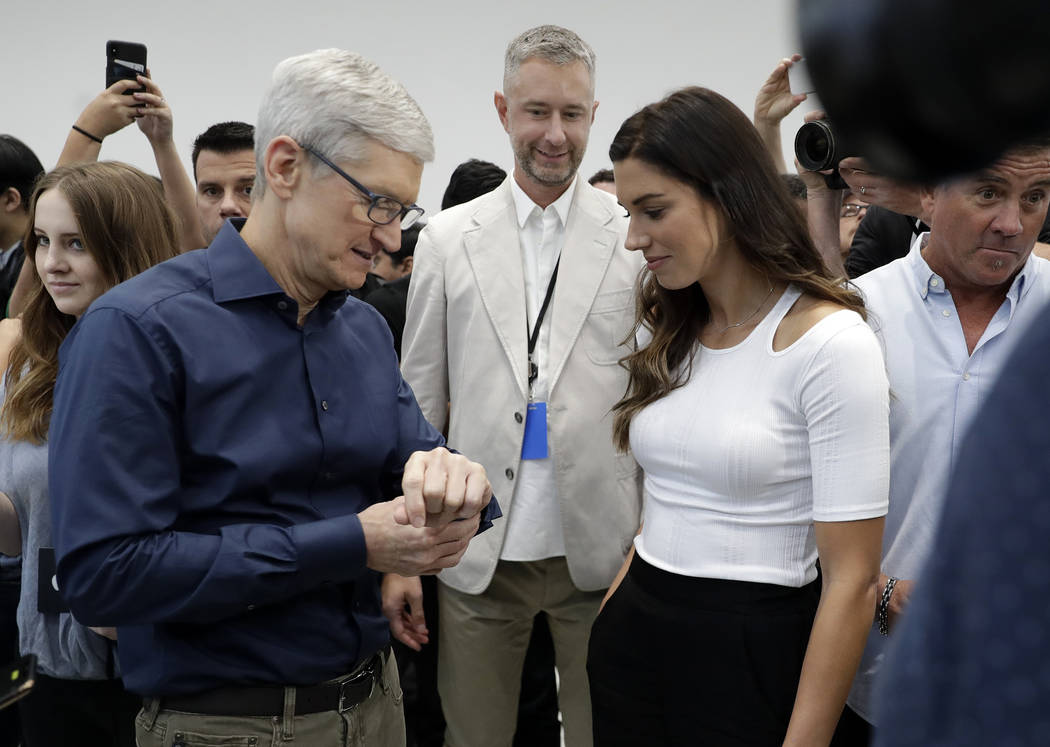 Apple CEO Tim Cook, left and soccer player Alex Morgan discuss the new Apple Watch 4 at the Steve Jobs Theater during an event to announce new products Wednesday, Sept. 12, 2018, in Cupertino, Cal ...