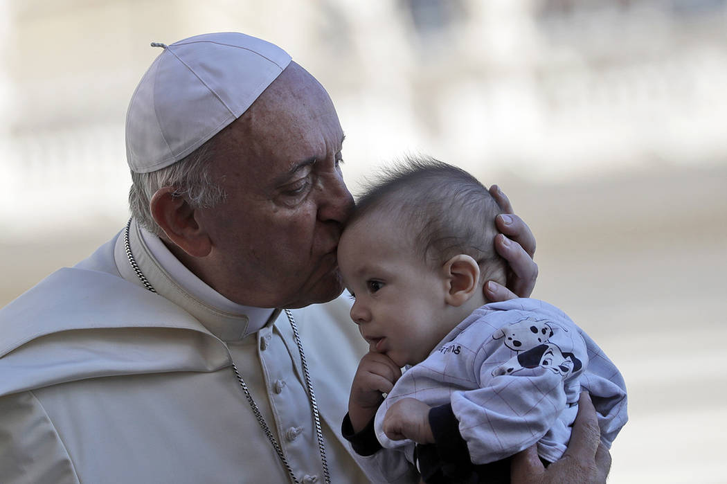 Pope Francis kisses a baby as he arrives in St. Peter's Square at the Vatican for his weekly general audience, Wednesday, Sept. 12, 2018. (AP Photo/Alessandra Tarantino)