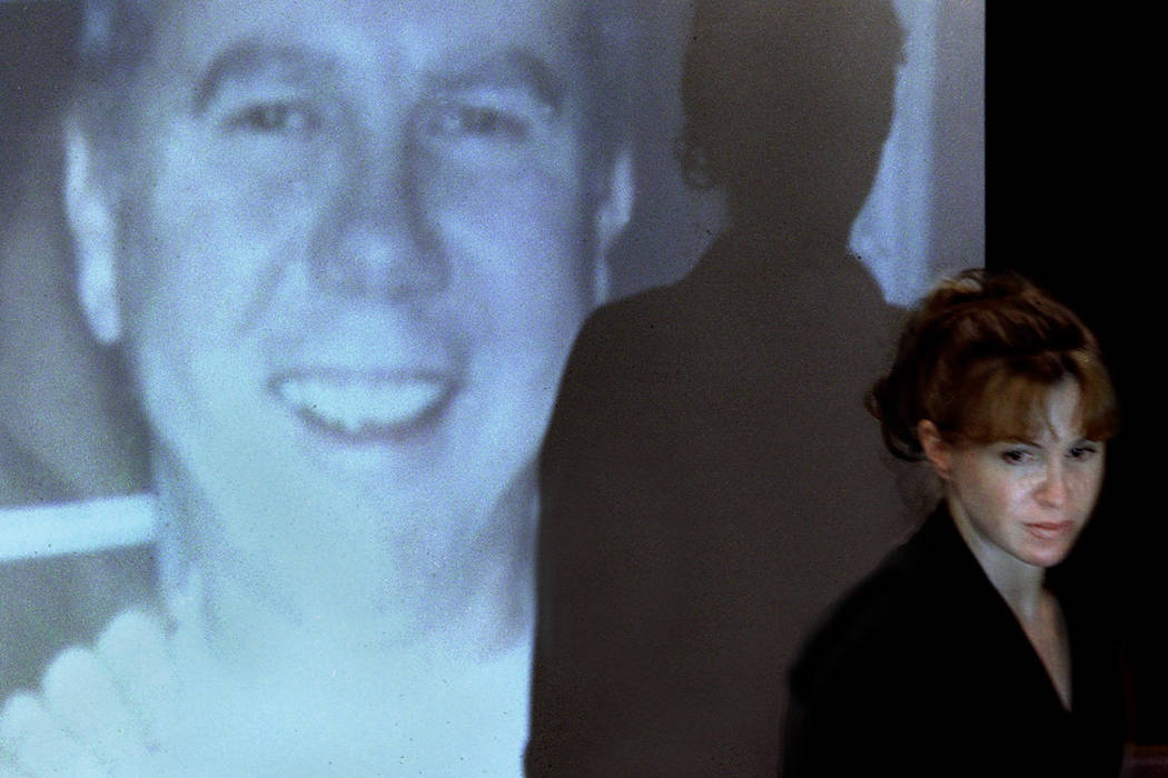 Sandy Murphy walks past a projected image of Ted Binion during the opening day of the murder trial in March 2000. (File Photo)