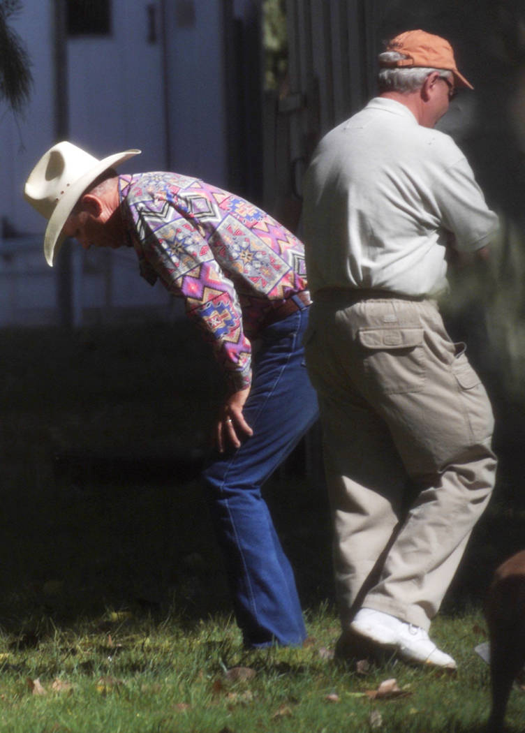 David Mattsen bends over while Tom Dillard, private investigator for the Ted Binion estate, walks past him during a search for buried treasure in Pahrump in September 2000. Nothing was found. (Fil ...