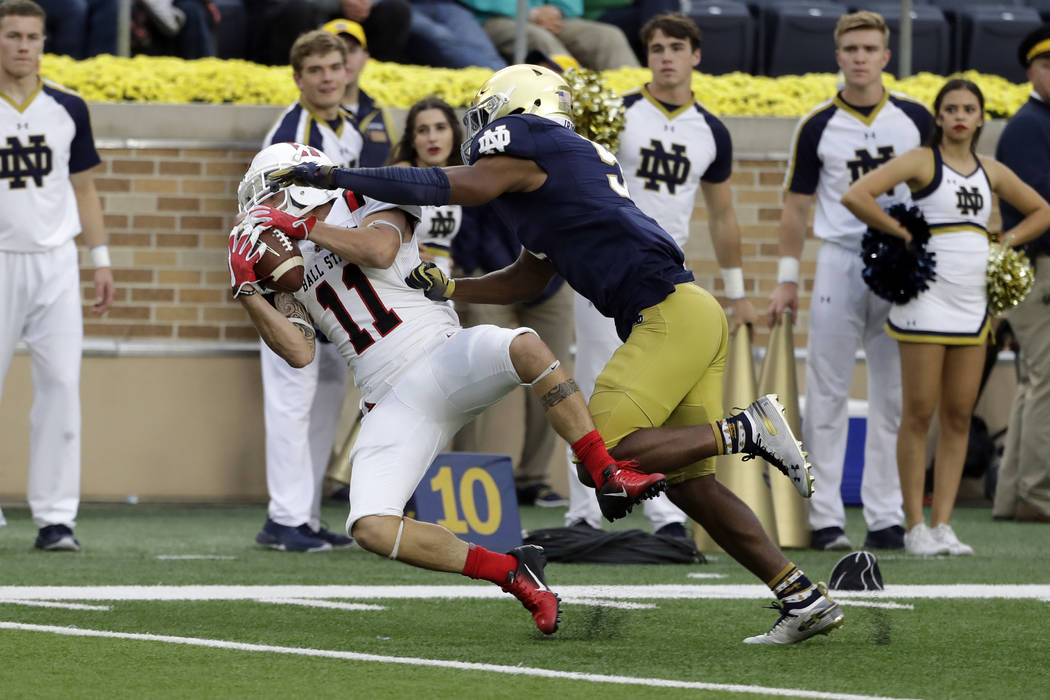 Ball State wide receiver Corey Lacanaria, left, catches the ball against Notre Dame cornerback Troy Pride Jr., during the second half of an NCAA college football game in South Bend, Ind., Saturday ...
