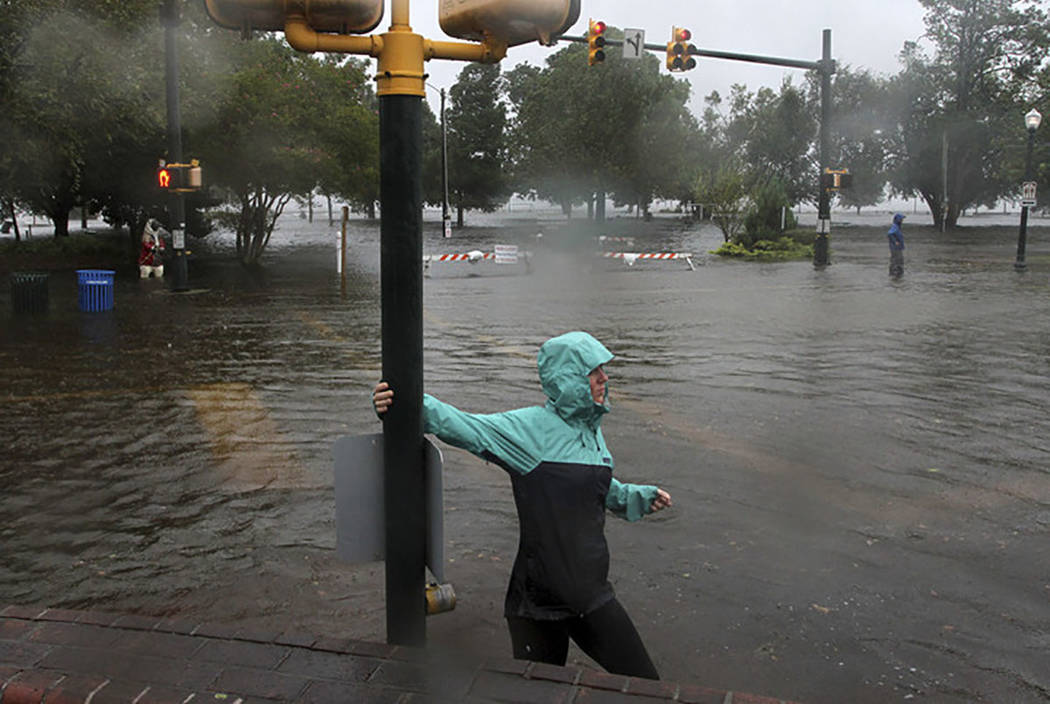 Jamie Thompson walks through flooded sections of East Front Street near Union Point Park in New Bern, N.C. Thursday, Sept. 13, 2018. (Gray Whitley/Sun Journal via AP)