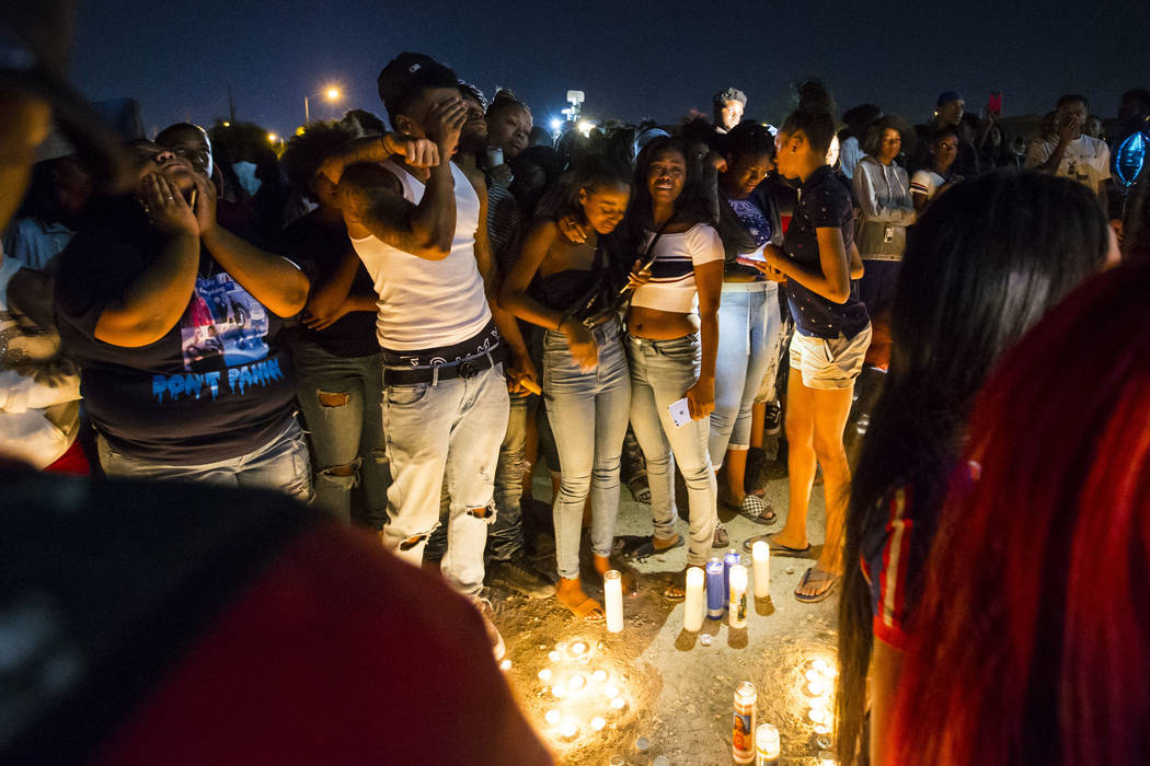 People mourn during a candlelight vigil in memory of Canyon Springs student Dalvin Brown, who was shot and killed this past Tuesday, outside of the school at Alexander Road and North 5th Street in ...