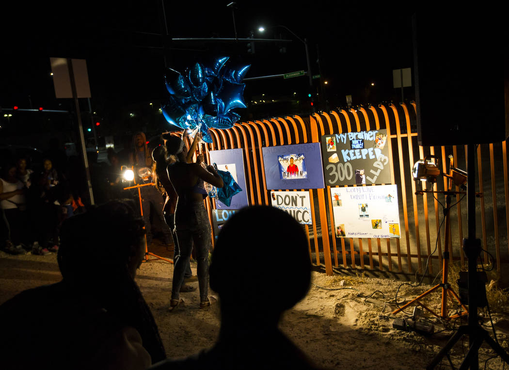 Attendees hang up balloons during a candlelight vigil in memory of Canyon Springs student Dalvin Brown, who was shot and killed this past Tuesday, outside of the school at Alexander Road and North ...