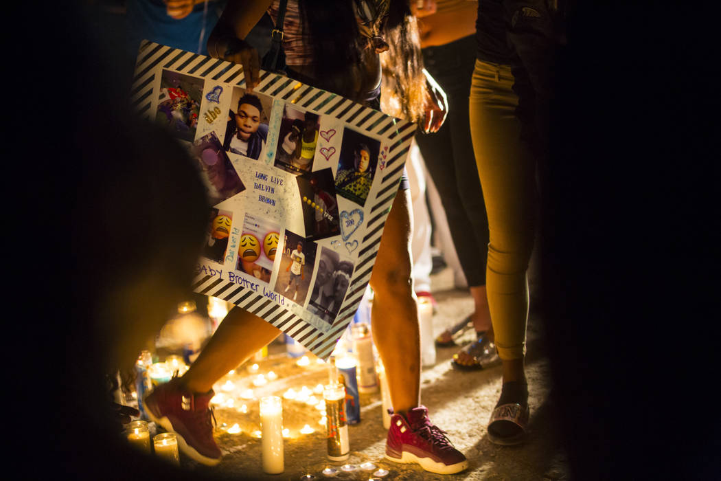 A poster with photos of Canyon Springs student Dalvin Brown, who was shot and killed this past Tuesday, is displayed during a candlelight vigil outside of the school at Alexander Road and North 5t ...