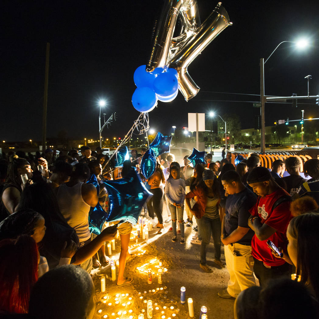 People gather during a candlelight vigil in memory of Canyon Springs student Dalvin Brown, who was shot and killed this past Tuesday, outside of the school at Alexander Road and North 5th Street i ...
