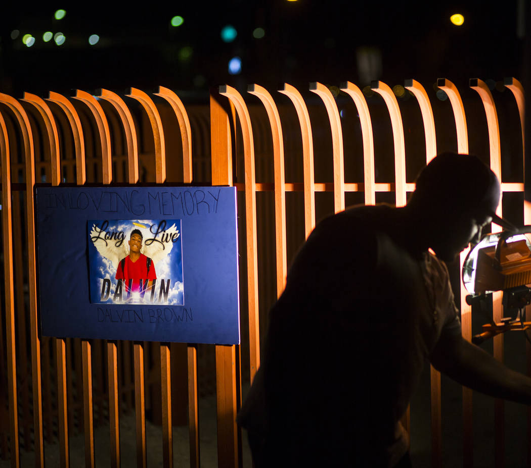 A poster with a photo of Canyon Springs student Dalvin Brown, who was shot and killed this past Tuesday, is displayed during a candlelight vigil outside of the school at Alexander Road and North 5 ...