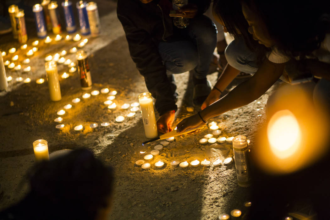 People light candles during a candlelight vigil in memory of Canyon Springs student Dalvin Brown, who was shot and killed this past Tuesday, outside of the school at Alexander Road and North 5th S ...
