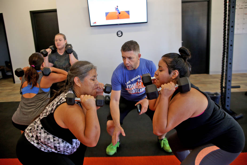 Head Coach Cory Drumright, center, instructs Irais Diego, left, and her daughter, Yohatzi Mendoza, right, perform dumbbell squats at a Tough Mudder Bootcamp class in Las Vegas, Sunday, Sept. 16, 2 ...
