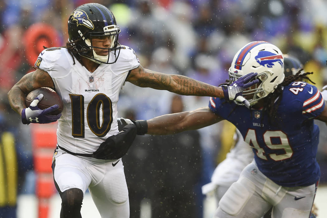 Baltimore Ravens wide receiver Chris Moore (10) carries the ball past Buffalo Bills linebacker Tremaine Edmunds (49) during the first half of an NFL football game between the Baltimore Ravens and ...