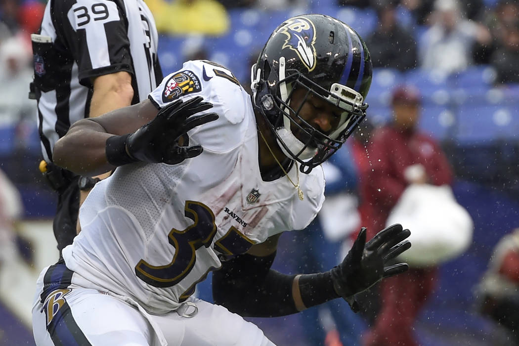 Rain drips off of Baltimore Ravens running back Javorius Allen's (37) helmet as he celebrates his touchdown during the second half of an NFL football game against the Buffalo Bills, Sunday, Sept. ...
