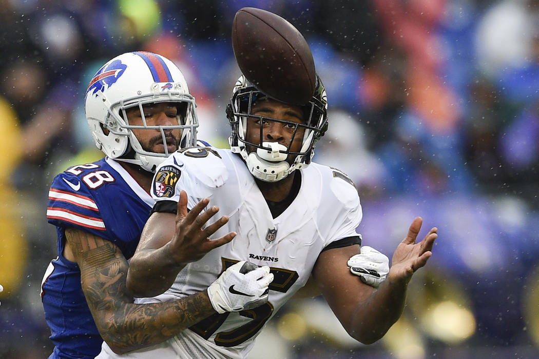 Baltimore Ravens wide receiver Michael Crabtree (15) reaches for a pass under pressure from Buffalo Bills defensive back Phillip Gaines (28) during the first half of an NFL football game between t ...