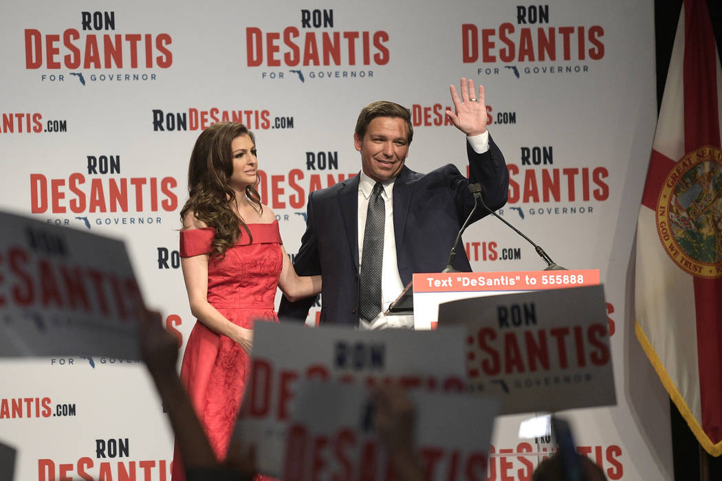 Florida Republican gubernatorial candidate Ron DeSantis, right, waves to supporters with his wife, Casey, at an election party after winning the Republican primary, Tuesday, Aug. 28, 2018, in Orla ...