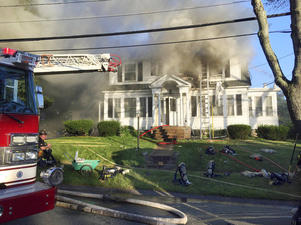 Firefighters battle a house fire, Thursday, Sept. 13, 2018, on Herrick Road in North Andover, Mass., one of multiple emergency crews responding to a series of gas explosions and fires triggered by ...