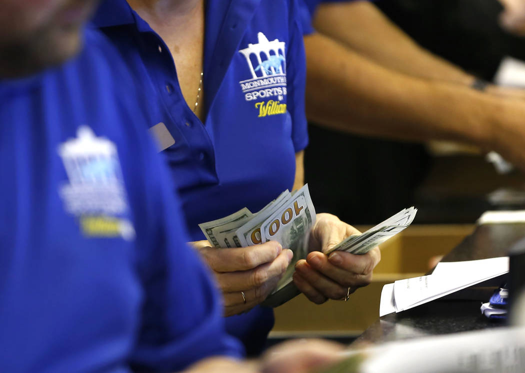 Ticket writers count cash before the opening of Monmouth Park Sports Book at Monmouth Park Racetrack, in Oceanport, N.J. on Thursday, June 14, 2018. (AP Photo/Noah K. Murray, File)