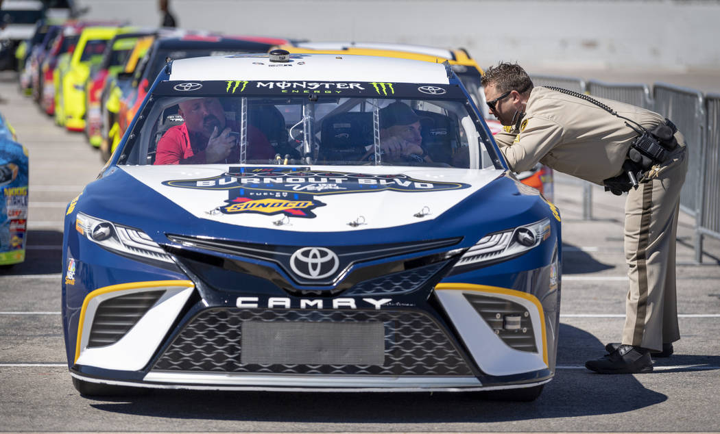 A Las Vegas Metro Police officer chats with drivers before the launch of the 2018 NASCAR Burnout Blvd introducing the NASCAR South Point 400 Weekend as cars are staged in the Las Vegas Convention ...