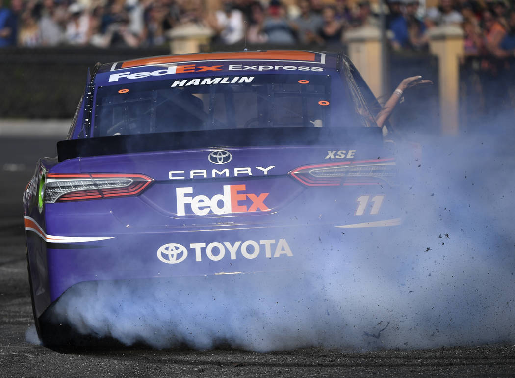 Denny Hamlin (11) throws smoke and rubber during the 2018 NASCAR Burnout Blvd event on the Las Vegas Strip at Spring Mountain Road Thursday, September 13, 2018. The event kicks off the Fall NASCAR ...