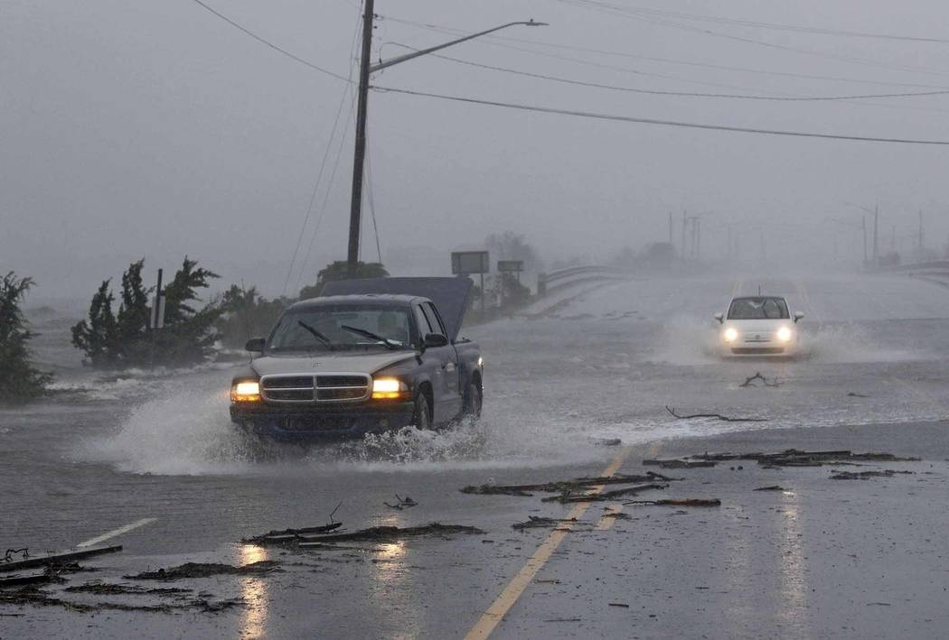 Vehicles drive through water from the White Oak River flooding Highway 24 as Hurricane Florence hit Swansboro N.C., Friday, Sept. 14, 2018. (AP Photo/Tom Copeland)