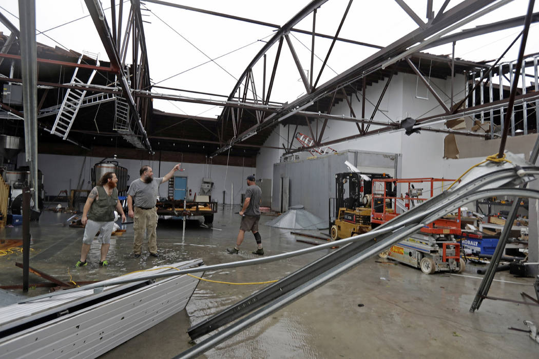 Ethan Hall, right, Michael Jenkins, center, and Nash Fralick, left, examine damage to Tidewater Brewing Co. in Wilmington, N.C., after Hurricane Florence made landfall Friday, Sept. 14, 2018. (AP ...