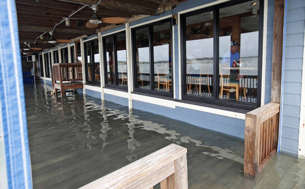 Sean Hayes, right, from Manteo, N.C., eats at Bubba's Seafood Restaurant with his family as the deck is covered with a few inches of water from effects of Hurricane Florence Friday, Sept. 14, 2018 ...