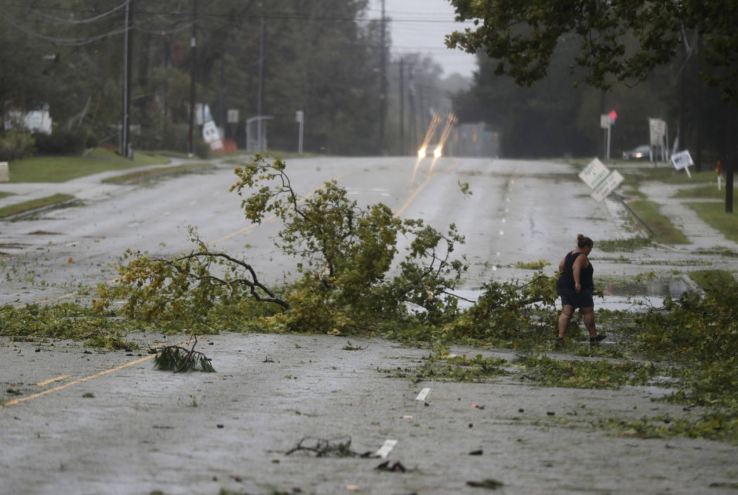 A woman removes debris from a road in Wilmington, N.C., after Hurricane Florence made landfall Friday, Sept. 14, 2018. (AP Photo/Chuck Burton)