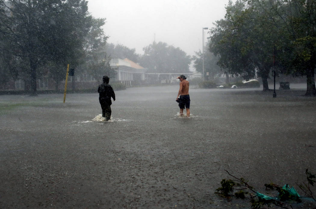 People walk through floodwaters caused by Hurricane Florence in downtown New Bern, N.C., on Friday, Sept. 14, 2018. (AP Photo/Chris Seward)