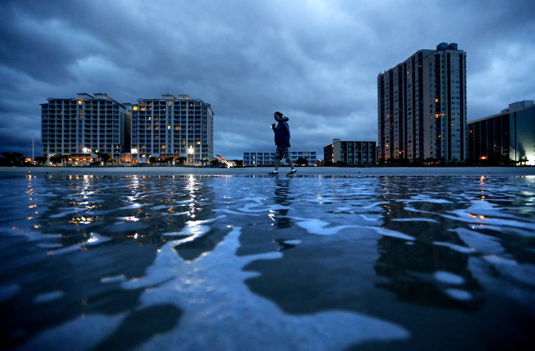 """Russ Lewis looks for shells along the beach as Hurricane Florence approaches Myrtle Beach, S.C., Friday, Sept. 14, 2018. """"We might get lucky we might not we'll find out,"""" said Lewis of t ..."""