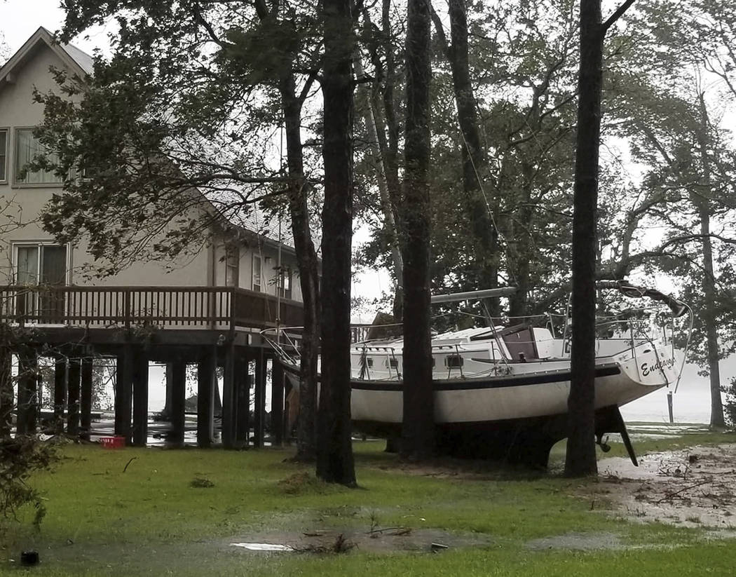 This photo provided by Angie Propst, shows a boat wedged in trees during Hurricane Florence in Oriental, N.C, one of nine incorporated municipalities in Pamlico County, Friday, Sept. 14, 2018. ( ...