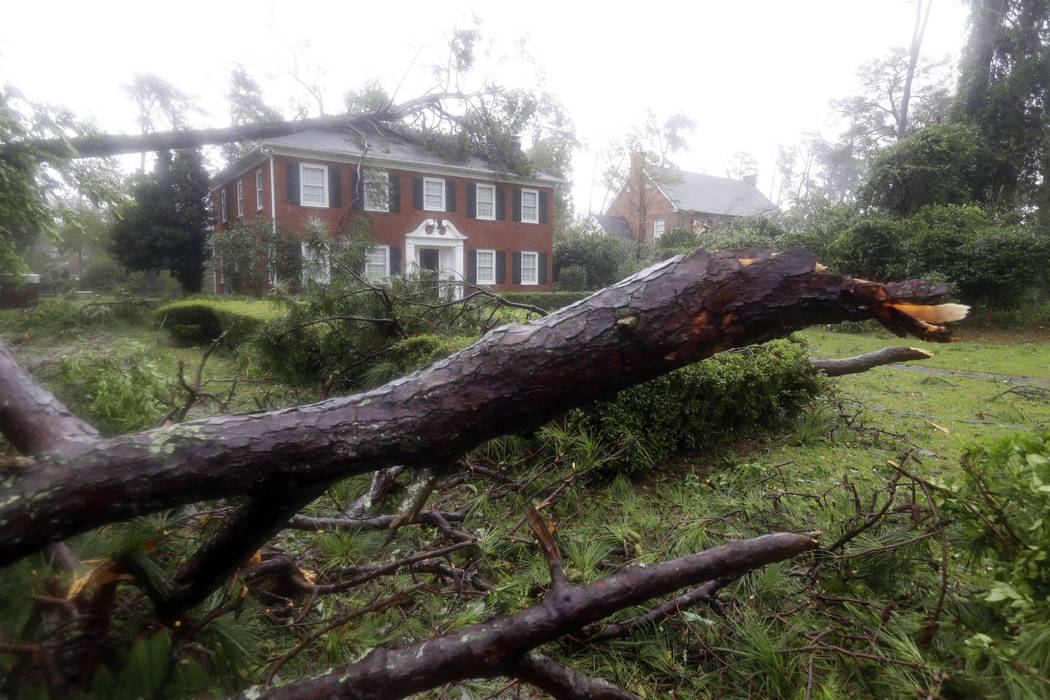 Toppled trees land in the yard and on a home in Wilmington, N.C., after Hurricane Florence made landfall Friday, Sept. 14, 2018. (AP Photo/Chuck Burton)