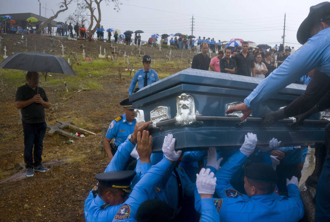 Police lift the coffin of fellow officer Luis Angel Gonzalez during his funeral at the cemetery in Aguada, Puerto Rico, Sept. 29, 2017. Gonzalez died when he tried to navigate a river crossing in ...