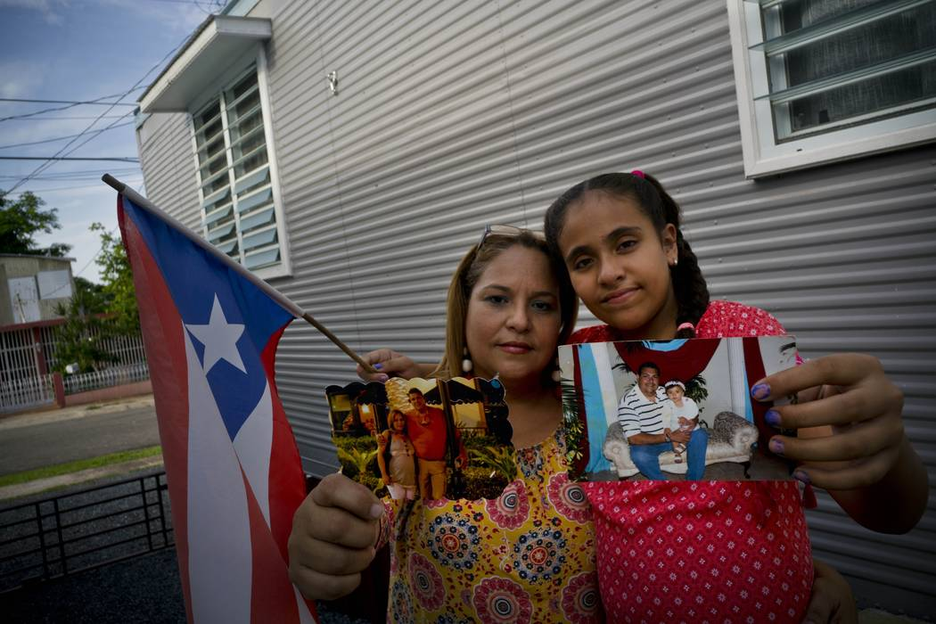 Lady Diana Torres, left, and her daughter Paula Nicole Lopez, pose with photos of their late husband and father Orlando Lopez Martinez, in Aguadilla, Puerto Rico, Sept. 5, 2018. Lopez, who died at ...