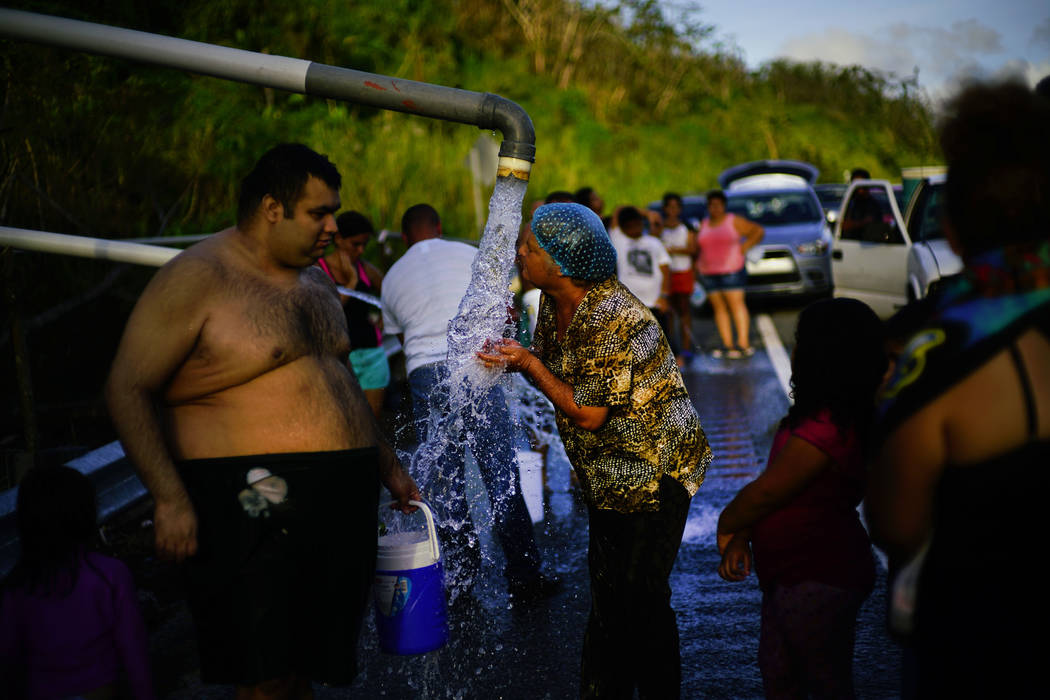 FILE - In this Oct. 14, 2017 file photo, people who lost access to water in the wake of Hurricane Maria gather at pipes carrying water from a mountain creek, on the side of the road in Utuado, Pue ...