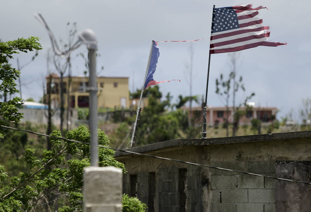 Deteriorated U.S. and Puerto Rico flags fly on a roof eight months after the passing of Hurricane Maria in the Barrio Jacana Piedra Blanca area of Yabucoa, a town where power was knocked out by th ...