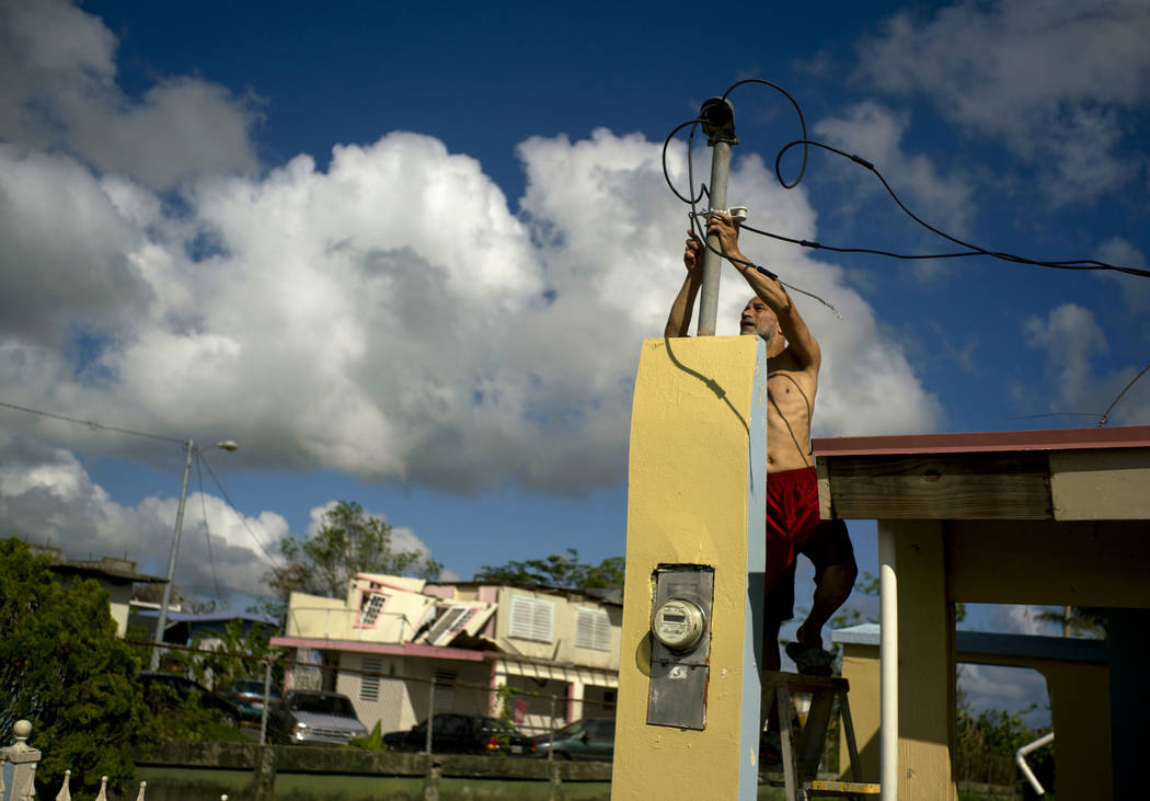 A resident tries to connect electrical lines downed by Hurricane Maria in preparation for when electricity is restored in Toa Baja, Puerto Rico, about three weeks after the storm, Oct. 13, 2017. L ...