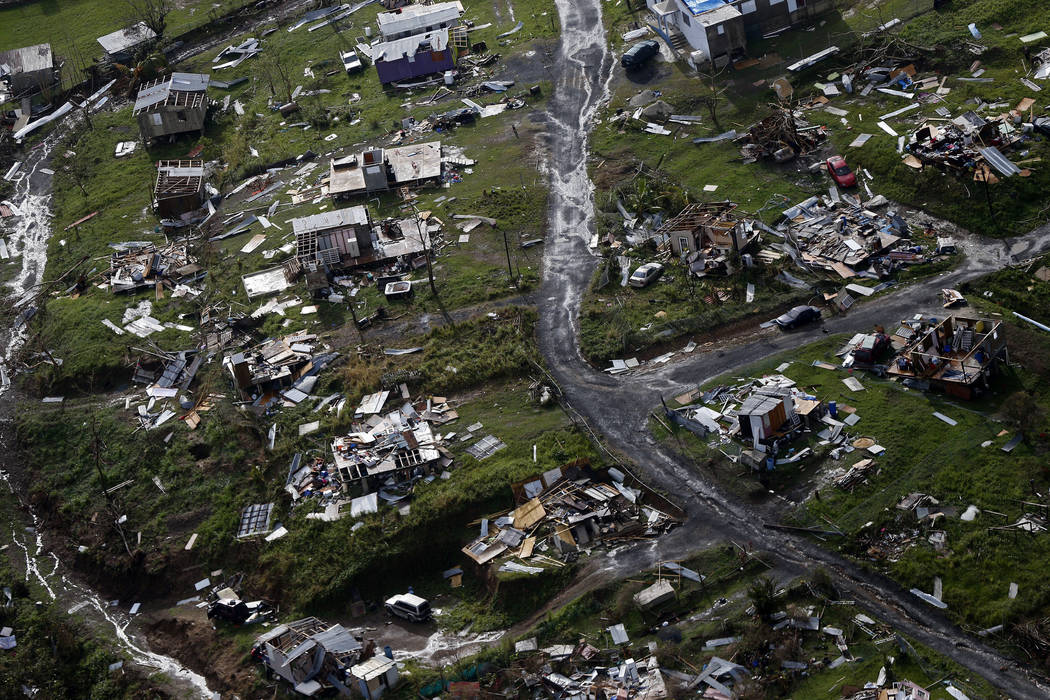 The rubble of homes are scattered in the aftermath of Hurricane Maria in Toa Alta, Puerto Rico, one week after the storm hit, Sept. 28, 2017. Puerto Rico's governor said one year after the storm t ...