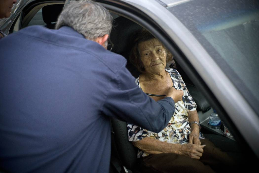 Carmen Hernandez, who lives in a senior living facility that lacks water and electricity in the wake of Hurricane Maria, is evaluated by a doctor after she fell, as she sits still for the doctor i ...